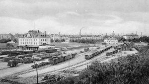 Vy från Oxelbergen över Östra stations nya och gamla stationshus. Vykort i Norrköpings stadsarkivs samlingar